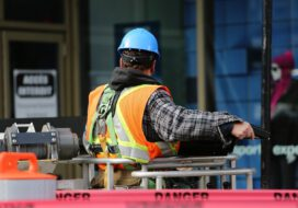 Pracownik budowlany w uprzęży i kasku, stoi na rusztowaniu.