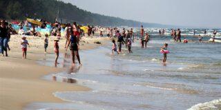 Nadmorska plaża. Wiele osób spaceruje brzegiem morza, część stoi w wodzie.