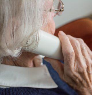 Starsza kobieta trzyma słuchawkę telefonu. Ujęcie z boku.