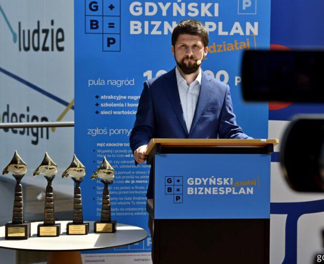 Redaktor portalu gdynia.pl stoi za mównicą ogłaszając wyniki konkursu Gdyński Biznesplan.