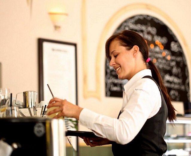 Kelnerka przygotwuje kawę z ekspresu.