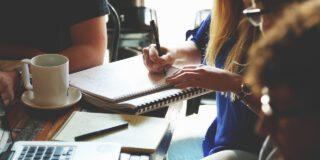 Biuro. Kilka osób pracuje w grupie. Na biurku znajduje się laprop oraz notesy i dokumenty.