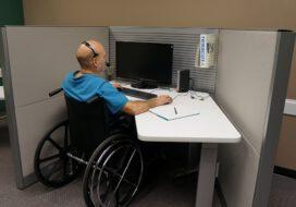 Osoba niepełnsprawna na wózku inwalidzkim pracuje przy biurku, na którym stoi komputer.